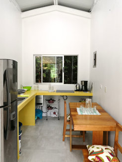Photo of the kitchen of Casita Hoja Verde with stove, fridge and dining table.