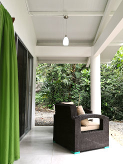 Photo of the terrace with entrances to the kitchen and a bedroom and an armchair facing the rainforest green