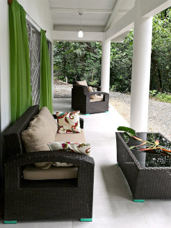 Photo of the terrace with armchair and sofa and the view into the green rainforest