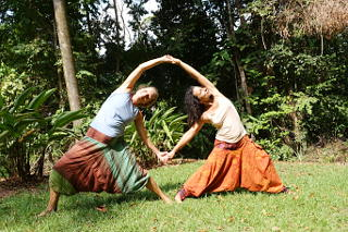 Two women in yoga exercises in the park surrounded by the jungle of Costa Rica