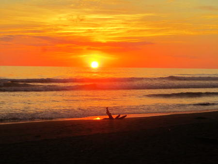 Photo from the beach with a red sunset over the Pacific Ocean.